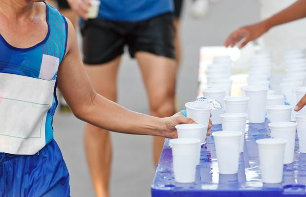 Marathon racer catching cup of water